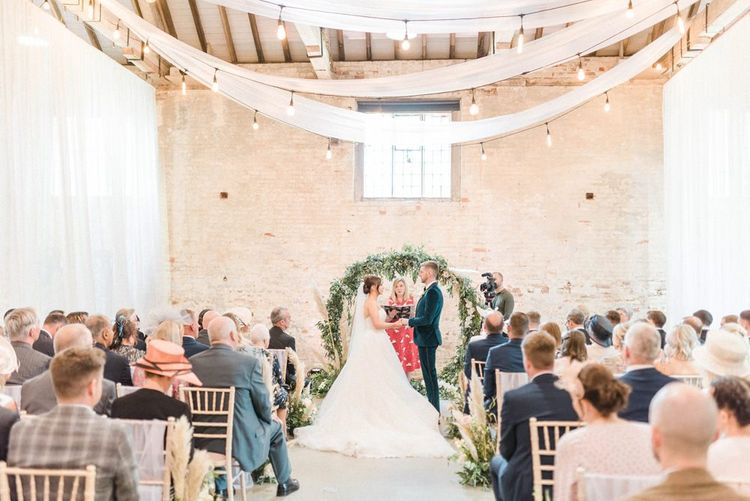 Wedding ceremony at Calke Abbey with drapes and moon gate