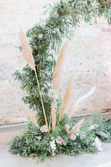 Foliage moon gate at ceremony with pampas grass