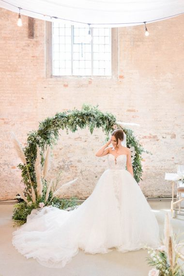 Bride in detachable skirt wedding dress in front of moon gate decor