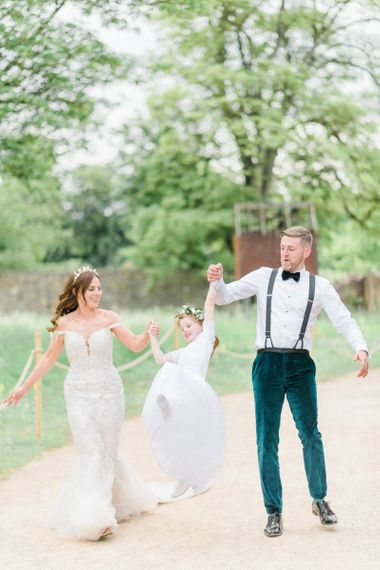 Bride in detachable skirt wedding dress with groom and flower girl