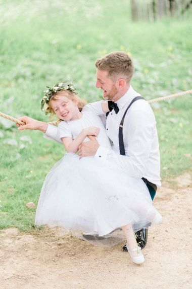 Groom and flower girl in white dress with flower crown