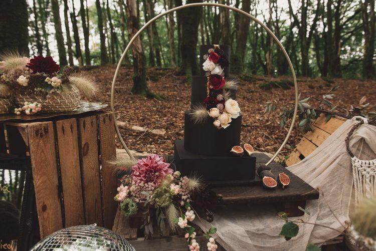 Black Wedding Cake with Flower Decor on Hoop Cake Stand