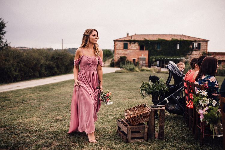 Bridesmaid in Dusky Pink ASOS Dress with Ruched Bodice and Off-Shoulder Straps | Pink, Purple and White Wildflower Bouquet Tied with Hessian and Lace | Outdoor Wedding Ceremony at Il Rigo Agriturismo, Tuscany | Rue de Seine Wedding Dress with Pronovias Overskirt, Personalised Place Setting Illustrations and Sweetheart Table | Samuel Docker Photography