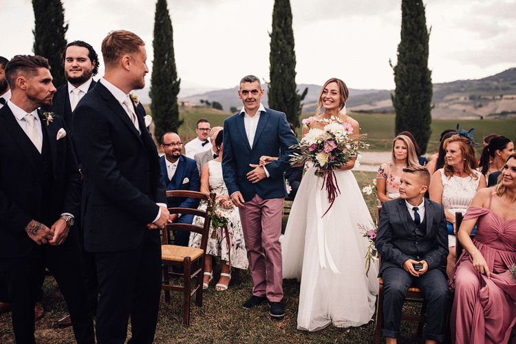 Bride in Structured Bustier Rue de Seine Fox Gown with Floral Appliqué Detail and Off The Shoulder Straps | Pronovias Chiffon Overskirt | Pink, Purple and White Wildflower Bouquet with White Trailing Ribbon | Groom in Three-Piece Hawes & Curtis Suit with Ivory Tie and Pocket Square | Outdoor Wedding Ceremony at Il Rigo Agriturismo, Tuscany | Rue de Seine Wedding Dress with Pronovias Overskirt, Personalised Place Setting Illustrations and Sweetheart Table | Samuel Docker Photography