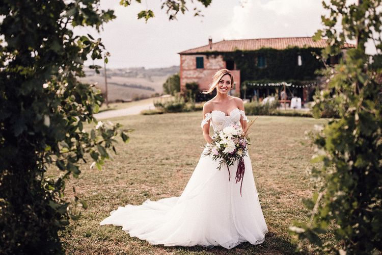 Bride in Structured Bustier Rue de Seine Fox Gown with Floral Appliqué Detail and Off The Shoulder Straps | Pronovias Chiffon Overskirt | Pink, Purple and White Wildflower Bouquet with White Trailing Ribbon | Il Rigo Agriturismo, Tuscany | Rue de Seine Wedding Dress with Pronovias Overskirt, Personalised Place Setting Illustrations and Sweetheart Table | Samuel Docker Photography