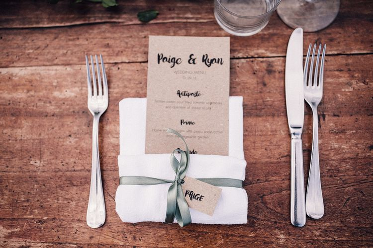 Kraft Paper Wedding Breakfast Menu | Kraft Paper Name Tag | Sage Green Ribbon | Table Runner with Pink Flowers and Foliage | Illustrated Place Setting in White Frame | Rue de Seine Wedding Dress with Pronovias Overskirt, Personalised Place Setting Illustrations and Sweetheart Table | Samuel Docker Photography