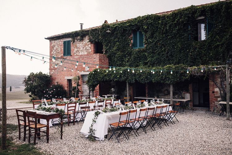 Long Banquet Tables | Sweetheart Table | Foliage Table Runners | Festoon Lights | Outdoor Wedding Reception at Il Rigo Agriturismo, Tuscany | Rue de Seine Wedding Dress with Pronovias Overskirt, Personalised Place Setting Illustrations and Sweetheart Table | Samuel Docker Photography