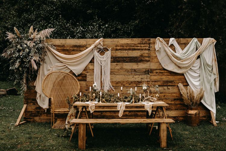 Wooden Backdrop with Drapes, Dried Flowers & Macrame Decor | Wooden Table with Candle Sticks & Greenery Garland | Nude Bohemian Wedding Inspiration by Wonderland Invites & Rock The Day Styling | Kelsie Low Photography
