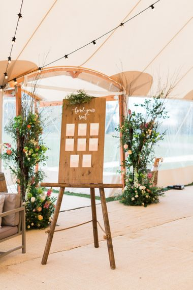Wooden Table Plan on an Easel with Festoon Lights & Floral Decor