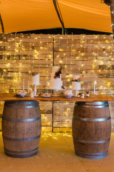 Cake Table on Barrels with String Lights Backdrop