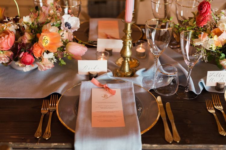 Elegant Place Setting with Gold Rimmed Platter, Blue Linen Napkin and Gold Cutlery