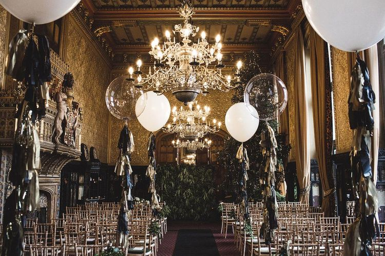Wedding Ceremony Room at Carlton Towers in Yorkshire with Giant Balloons and Tissue Tassels, Christmas Tree and Foliage Wall Backdrop