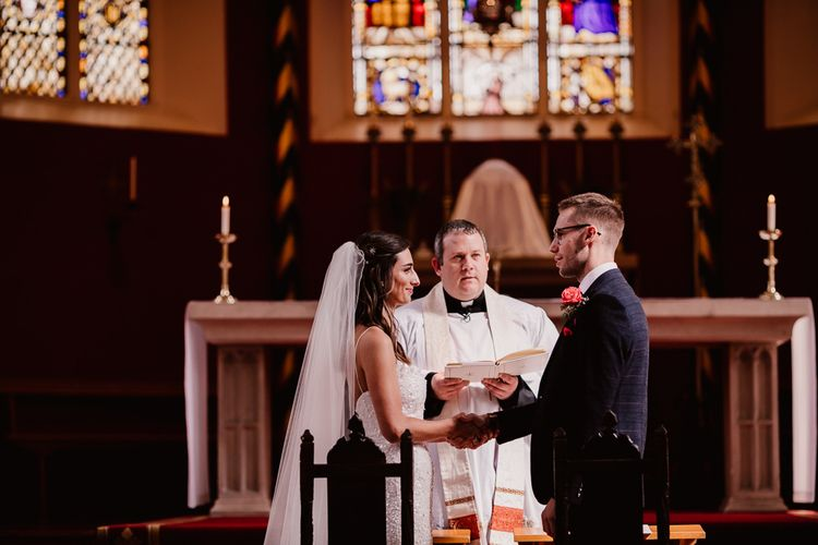 Bride and Groom Exchange Vows At Church Ceremony