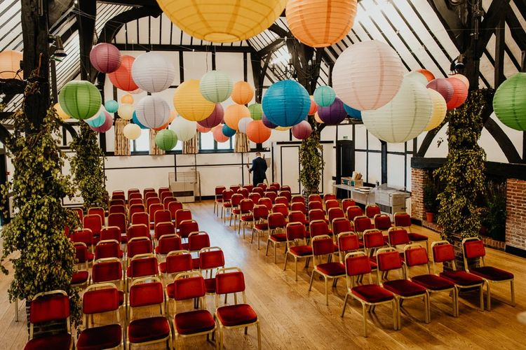 Colourful hanging lanterns at village hall wedding with bright dahlia floral decor