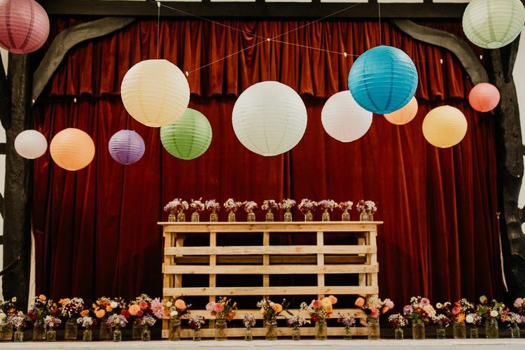 Brightly coloured hanging lanterns at village hall wedding with wooden display and floral decor