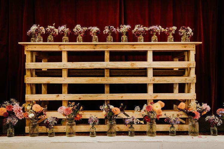 Brightly coloured dahlia decor on wooden display at village hall wedding