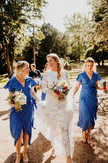 Bride wearing long sleeved laced dress and gold ballet pumps with her bridesmaids wearing blue star print dresses