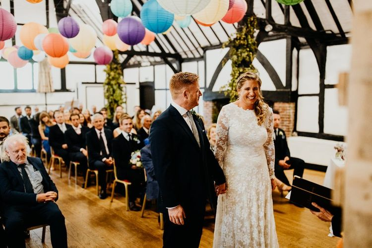 Bride and groom tie the knot at village hall ceremony with colourful hanging lanterns