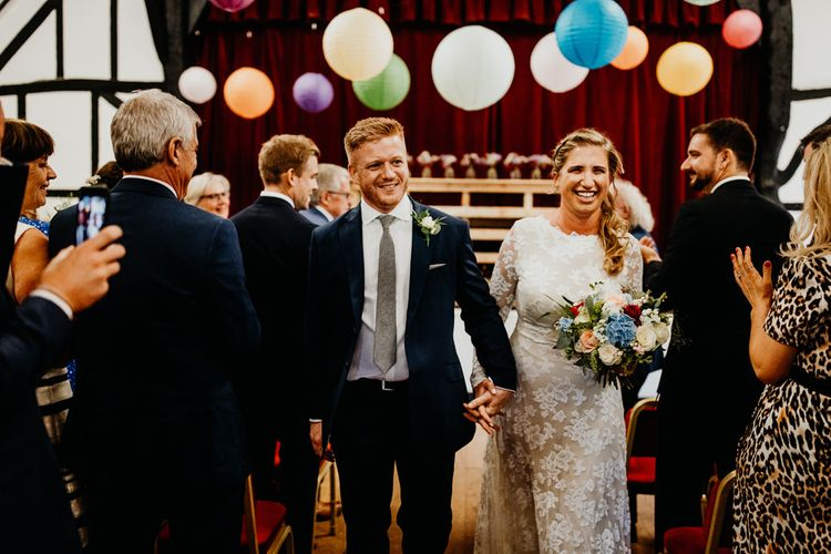 Groom wearing navy two piece with the bride wearing laced long sleeve dress and brightly coloured floral bouquet