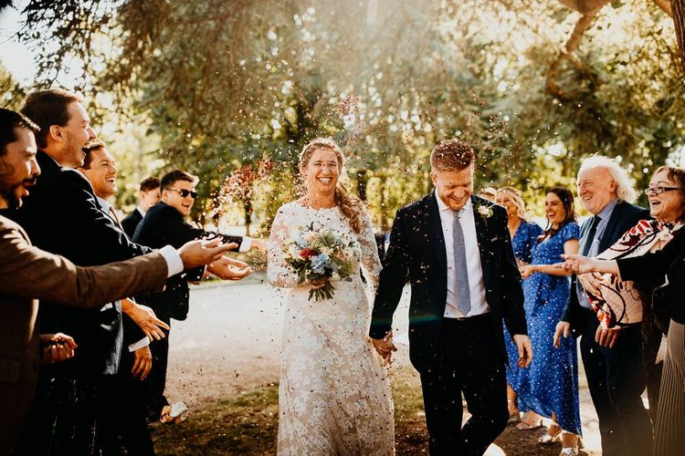 Confetti shot at village hall wedding with bride wearing long sleeved laced dress