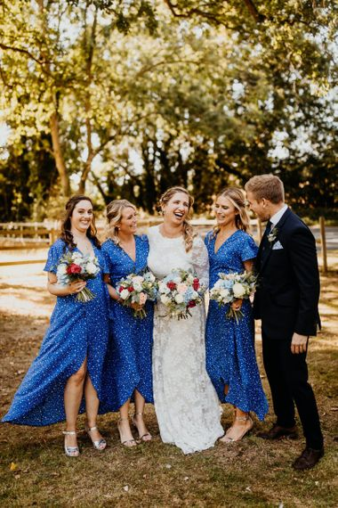 Bridesmaids wearing blue star print dresses with silver shoes and colourful floral bouquets