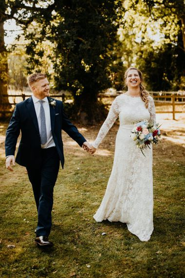 Bride and groom steal a moment at village hall wedding wearing laced long sleeve dress and bright floral bouquet