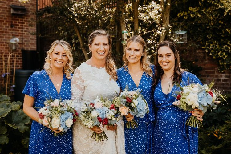 Bride and her bridesmaids wearing star print dresses and bright floral bouquets