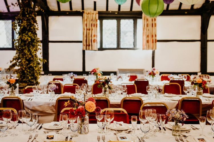 Village hall wedding reception with floral table arrangements of colourful dahlias and hanging lanterns