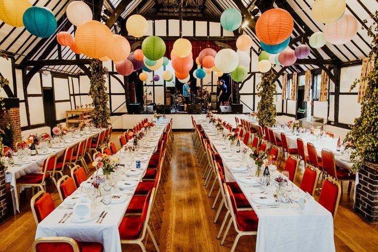Hanging lanterns and colourful floral arrangements at village hall wedding reception