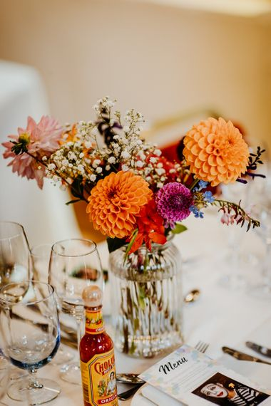 Brightly coloured floral table arrangements of dahlias and gypsophila with hanging lanterns
