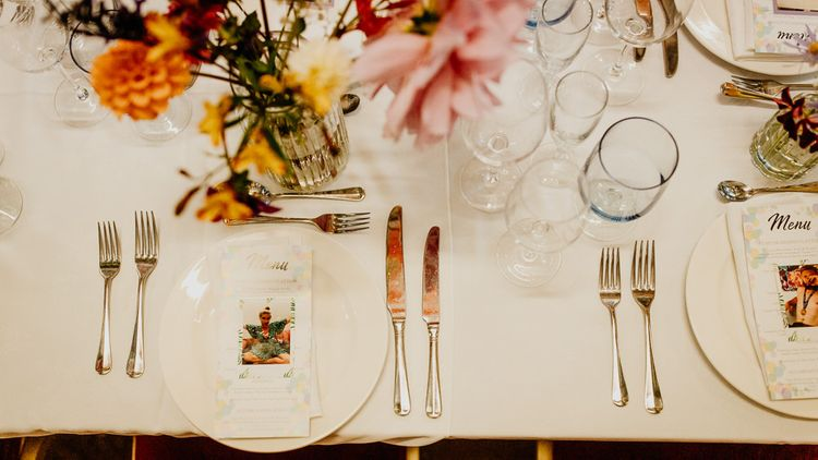 Personalised polaroid image place settings at village hall wedding with bright and colourful styling and hanging lanterns