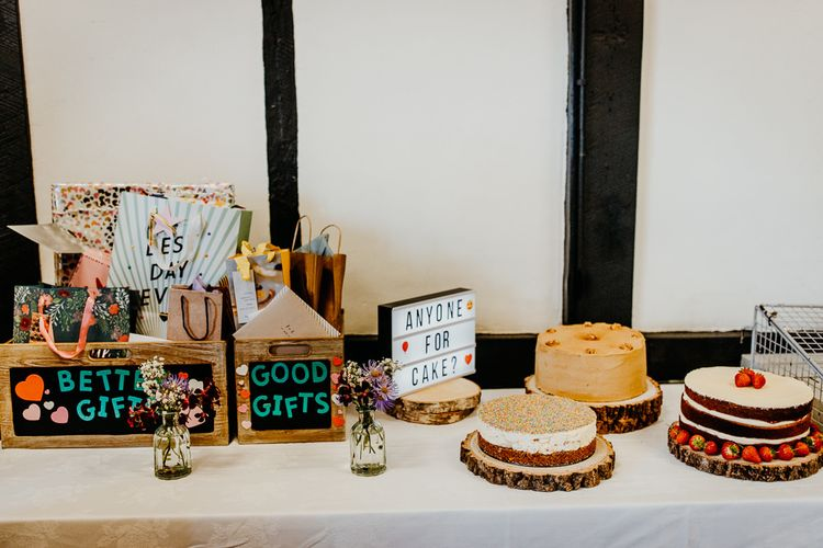 Gift boxes and wedding cakes at village hall wedding with colourful styling and hanging lanterns