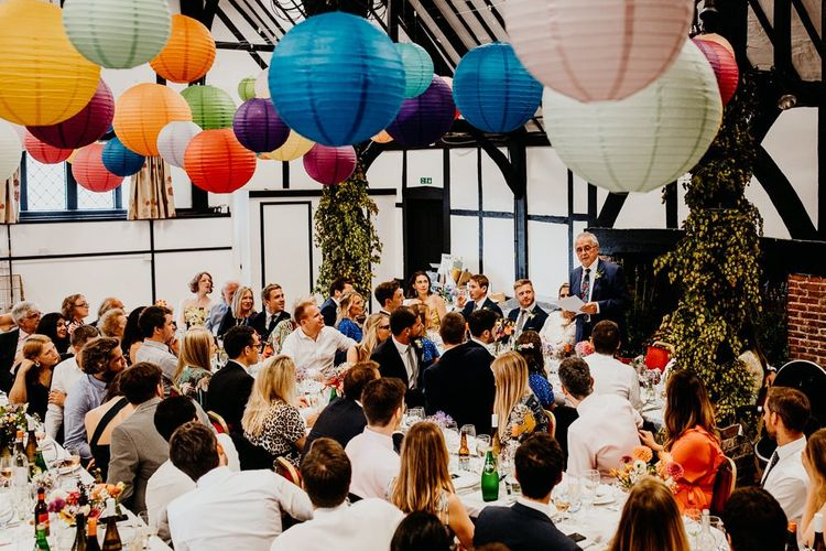 Colourful hanging lanterns decorate the ceiling at village hall reception
