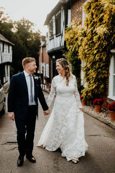 Bride wearing laced long sleeve dress and groom wearing navy two piece suit