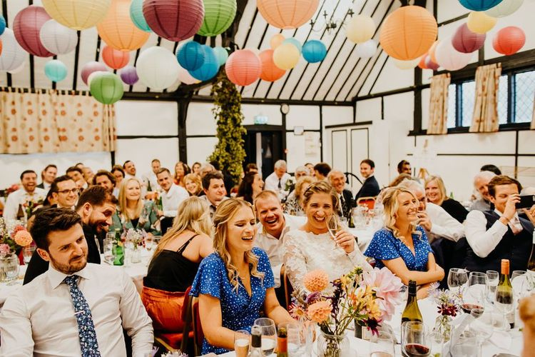 Bright and colourful hanging lanterns decorate the ceiling at village hall wedding