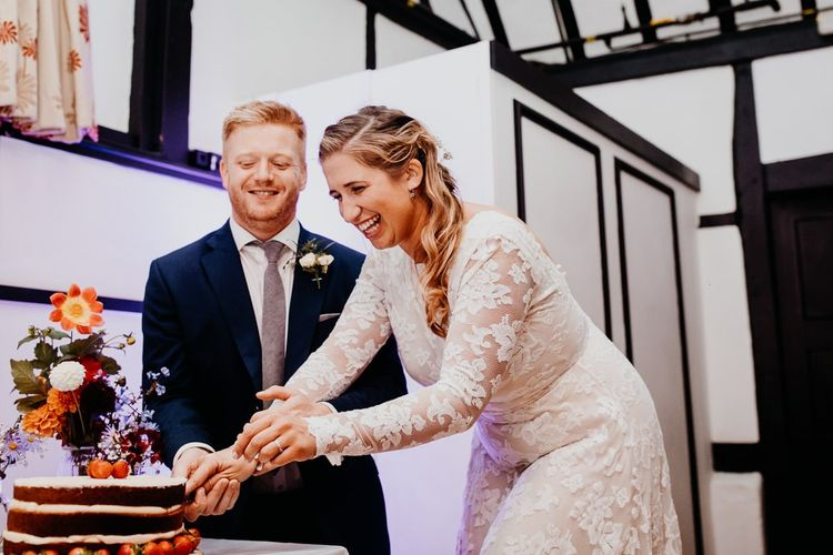 Bride and groom cut the cake decorated with berries and colourful florals