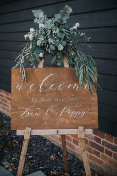 Wooden Welcome Sign on an Easel with Green Eucalyptus and Foliage Decor
