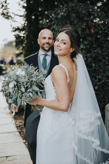Bride on Lace Enzoani Wedding Dress with Green Foliage Wedding Bouquet