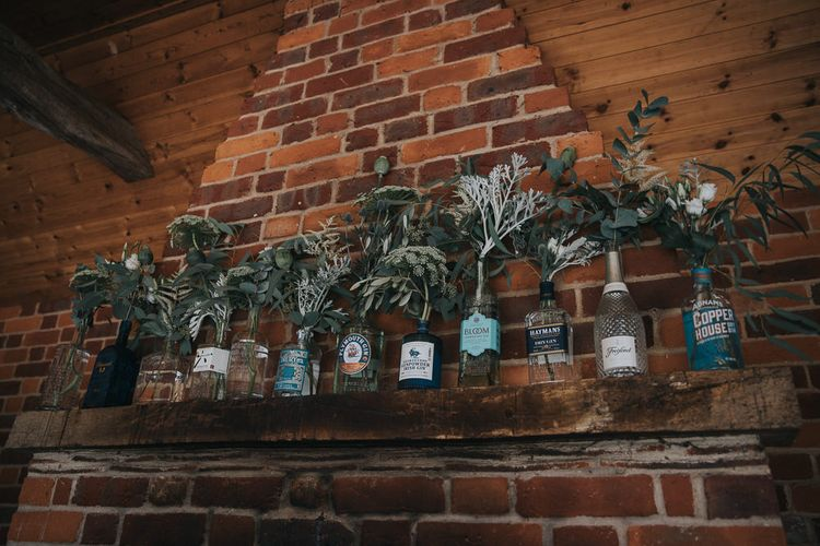 Foliage Filled Gin Bottles Wedding Decor