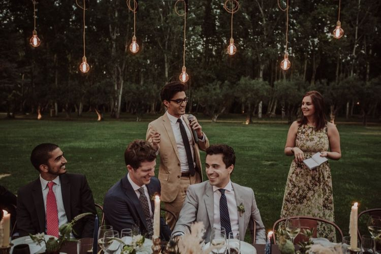 Outdoor Wedding Reception Speeches with Festoon Lights | Woodland Wedding Ceremony at Sa Farinera de Sant LLuis Wedding Venue, Catalan Empordà, Spain | Planned & Styled by Mille Papillons | HUMà06 Photography | HUMà06 Photography