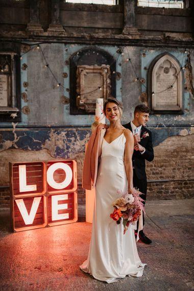Bride in Minimalist Wedding Dress and Pink Wedding Jacket
