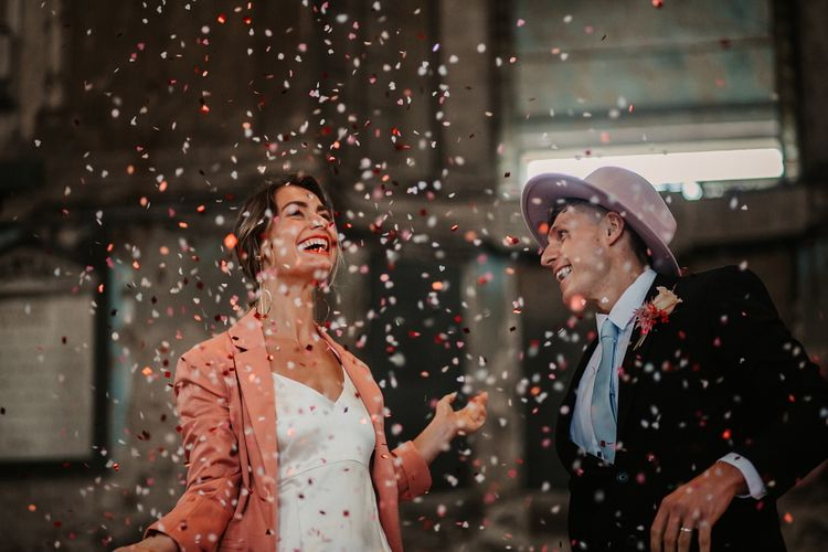 Confetti Bomb Moment with Bride in Pink Wedding Jacket and Groom in Fedora Hat