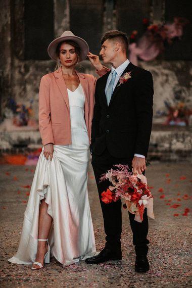 Stylish Bride and Groom in Minimalist Wedding Dress, Pink Wedding Jacket and Fedora Hat