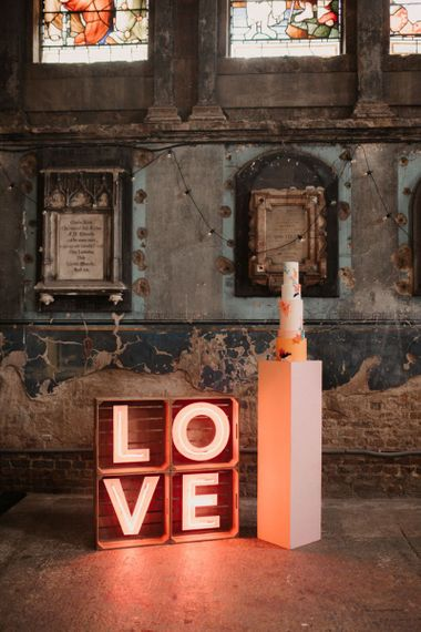 LOVE Neon Sign with Tall Wedding Cake on a Plinth