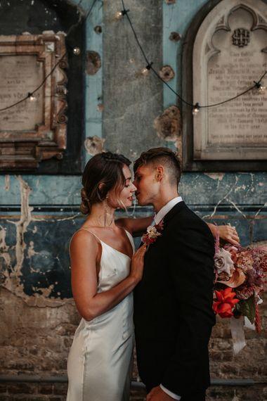 Bride and Groom Kissing Under Festoon Lights