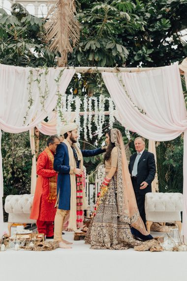 Indian Bride and Groom Exchanging Vows Under a Mandapa Mandap