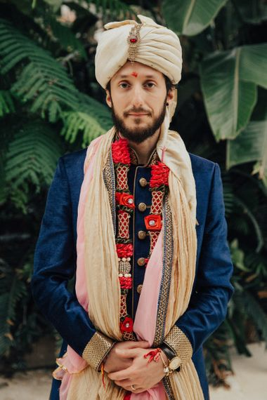 Groom in Traditional Navy and Gold Suit and Turban