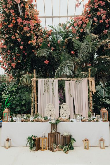 Botanical Top Table Wedding Decor With Bamboo Backdrop  and Wooden Crate  and Hurricane Lamps