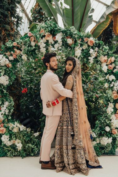 Bride in Gold Saree and Groom in Beige Suit Standing in Front of Floral Moon Gate