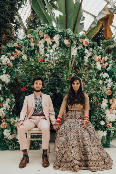 Bride in Gold Saree and Groom in Beige Suit Sitting in Front of Floral Moon Gate